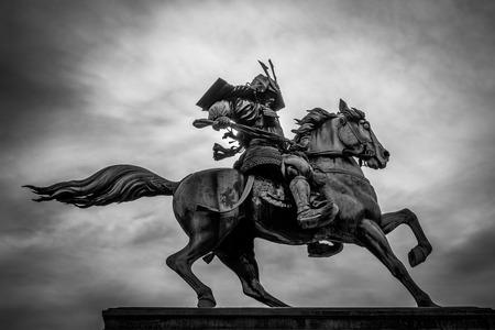 Black and white of a samurai on horseback.