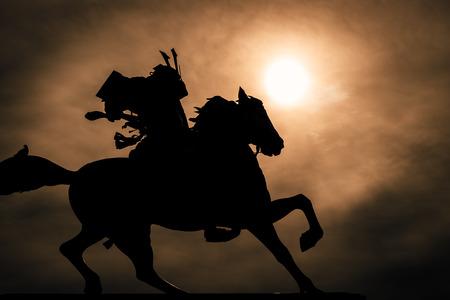 Zwart-wit silhouet van een samoerai te paard.