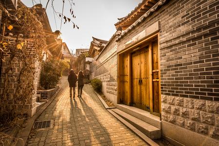 Een paar vrouwen dwalen door de traditionele stijl huizen van Bukchon Hanok Village in Seoul, Zuid-Korea.