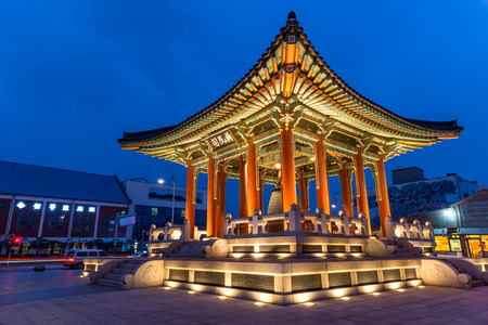 korean culture: The bell pavilion of Hwaseong Fortress lit up as evening comes on.
