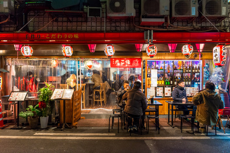 Locals eat a late night dinner outside a restaurant on December 27, 2014 in Osaka, Japan.