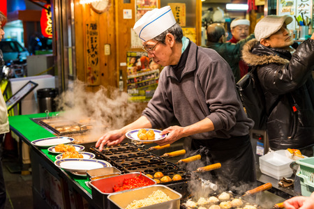 A Japanese man grills takoyaki at a food stall on December 27, 2014 in Osaka, Japan.