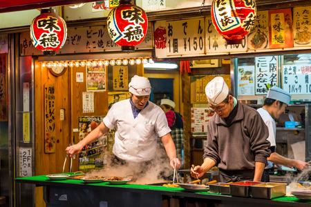 Mannen koken traditionele Japanse straat eten op 27 december 2014 in Osaka, Japan. Redactioneel