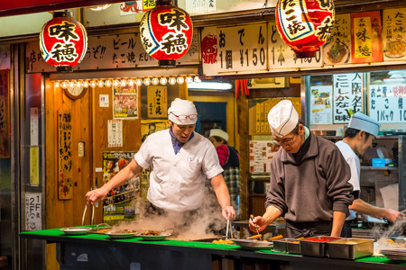 Men cook traditional Japanese street food on December 27, 2014 in Osaka, Japan. 新聞圖片