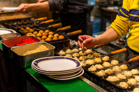Takoyaki being grilled at a street food stall in Osaka, Japan. Stock Photo