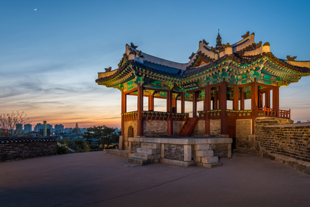 south korea: A watchtower at Hwaseong Fortress lit up at sunset in Suwon, South Korea.