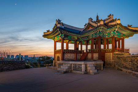 Een wachttoren bij Hwaseong Fortress verlicht bij zonsondergang in Suwon, Zuid-Korea. Redactioneel