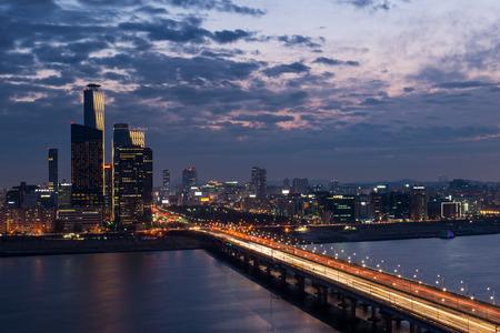 urban sprawl: Traffic blurs across a bridge on the Han River as dusk settles in over Seoul, South Korea. Stock Photo