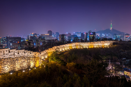 urban sprawl: The old city wall lit up in evening as the lights of downtown Seoul shine in the distance.