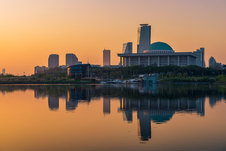 megacity: The sun rises over the National Assembly of South Korea in the Yeouido district of Seoul. Stock Photo