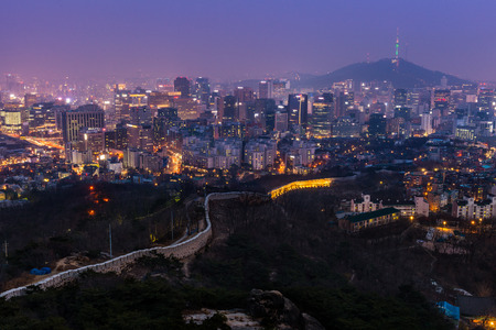 atop: The view over downtown Seoul at dusk from atop Mount Inwangsan. Stock Photo