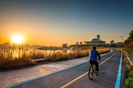 ciclista: Un ciclista paseos a lo largo del r�o Han de Se�l, Corea del Sur, por la ma�ana temprano. Foto de archivo