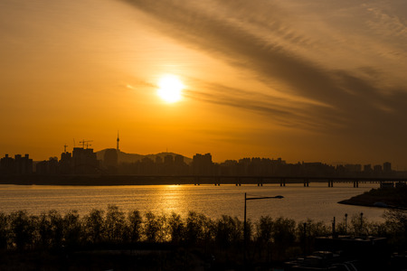 megacity: The sun rises over the Han River and Namsan Tower in the far distance in Seoul, South Korea.