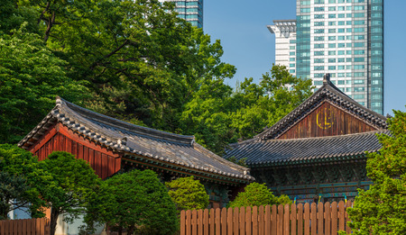 newer: The old architecture of Bongeunsa Temple stands against the newer skyscrapers of Gangnam in Seoul, South Korea. Stock Photo