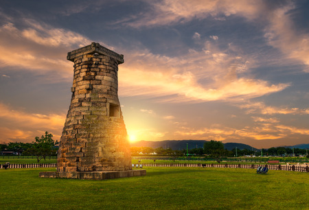 The sun sets behind Cheomseongdae Observatory in Gyeongju, South Korea. The observatory dates to the seventh century and is a national treasure of Korea. Stock Photo