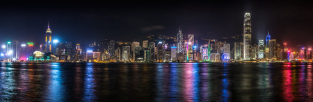 Panorama of the Hong Kong skyline lit up at night along Victoria Harbor.