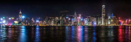 Panorama van de skyline van Hong Kong 's nachts verlicht langs Victoria Harbor.