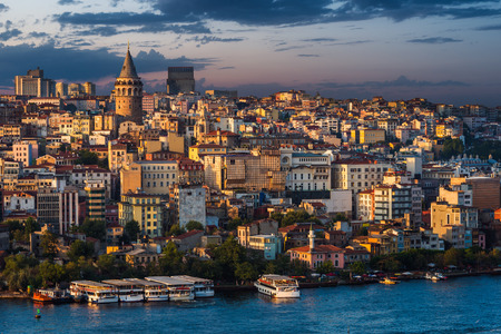 istanbul: Galata Tower lit up in early evening along the Golden Horn in Istanbul, Turkey. Stock Photo