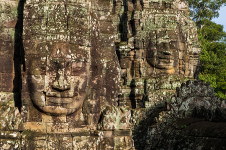 heritage site: The ancient stone faces of the Bayon within the Angkor Thom temple complex in Siem Reap, Cambodia.