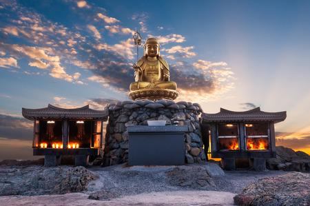 De zon komt achter een standbeeld van Boedha bij Haedong Yonggungsa Temple in Busan, Zuid-Korea.