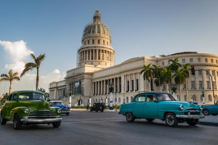 la: Old American cars drive past the Capitol building in Havana, Cuba. Stock Photo