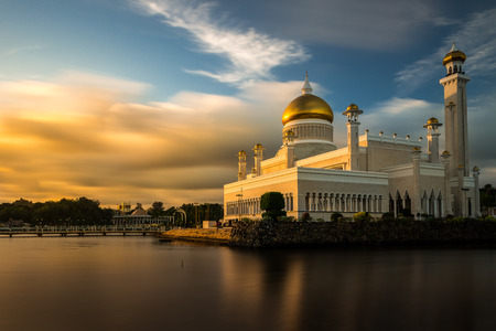 The late afternoon sun sets over Bandar Seri Begawan, Brunei, and strikes the facade of the Sultan Omar Ali Saifuddin Mosque. 스톡 콘텐츠