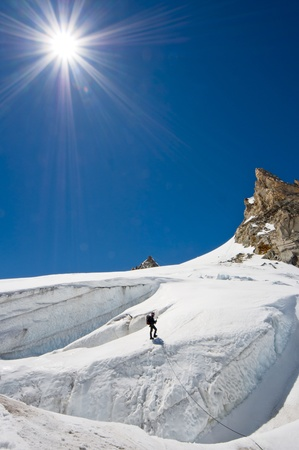 A male climber , dressed in black, climbs up a snowy slope. Winter clear sky day. photo
