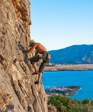 climber while climbing a vertical rock wall photo