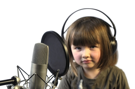 microphone  in focus  and little girl getting ready to record  out of focus  photo