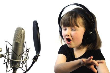 actief luisteren: klein meisje verdiept in het opnemen van een lied Stockfoto