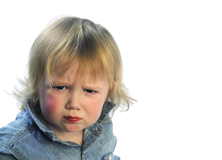 unsatisfied: Portrait of unsatisfied toddler on white background Stock Photo