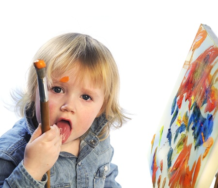Portrait of a child painting on canvas and eating paint photo