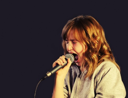 Girl Holding a microphone, singing on dark background photo