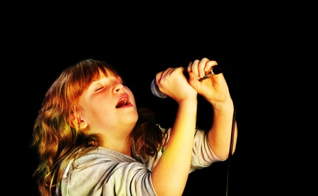 vocals: Girl Holding a microphone, singing on dark background Stock Photo