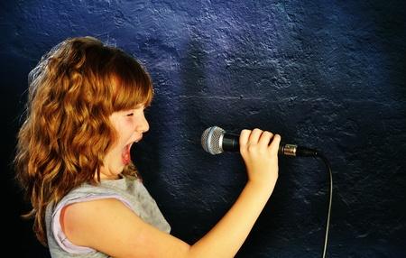 Chica celebraci�n de un micr�fono, cantando sobre un fondo oscuro photo