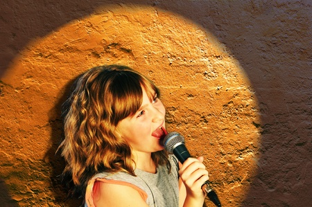 Girl Holding a microphone, singing in spotlight photo
