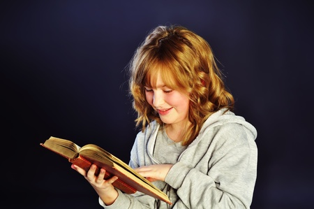 Girl reading an old book on dark background Stock Photo - 13490532