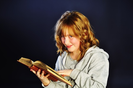 Girl reading an old book on dark background Stock Photo - 13490533