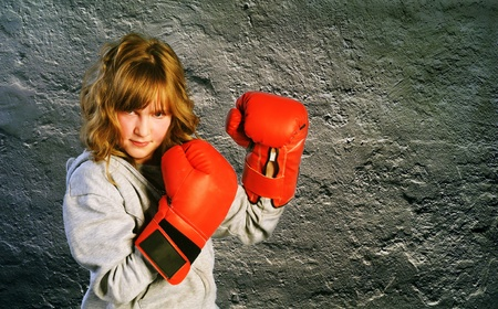 Girl wearing red boxing gloves on dark background photo