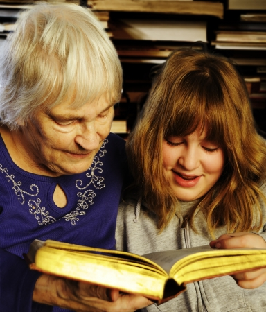 teenage girl and senior woman reading a book together photo