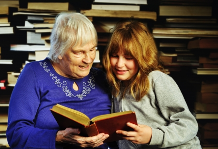 teenage girl and senior woman reading a book together Stock Photo - 13621196