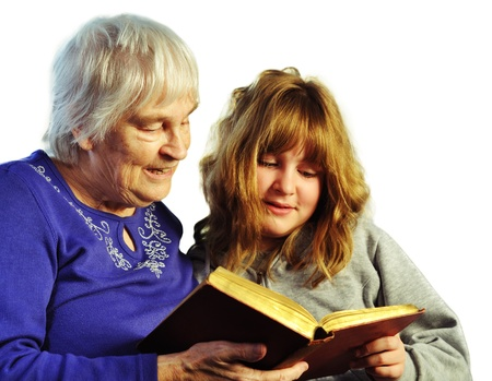 teenage girl and senior woman reading a book together Stock Photo - 13621191