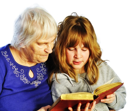 teenage girl and senior woman reading a book together Stock Photo - 13621195