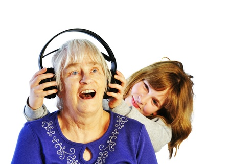 senior woman and young girl listening to the music through headphones on white background photo