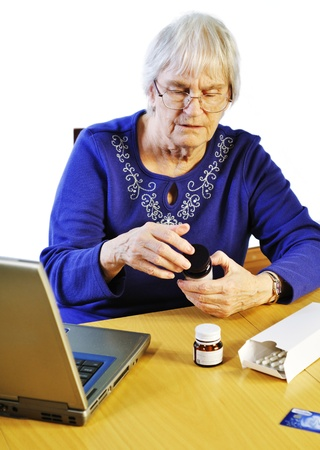 senior woman buying her medication on-line photo