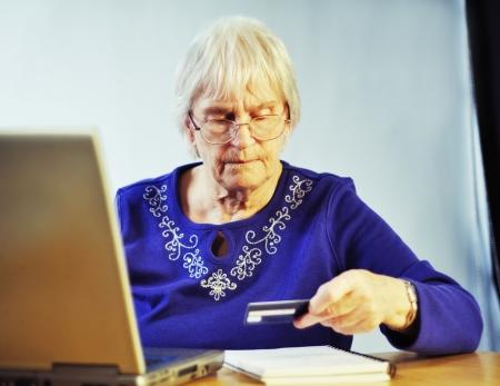senior woman paying after using internet shopping photo