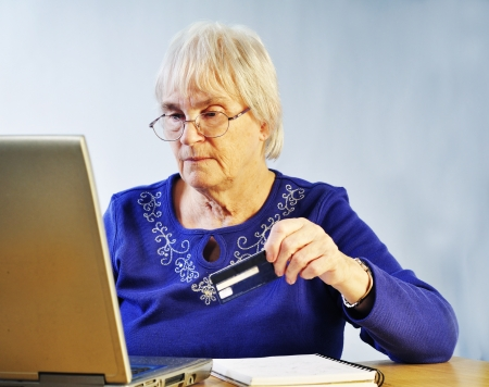 senior woman paying after using internet shopping photo