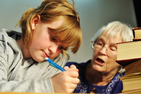 A senior woman helping a girl with her homework photo