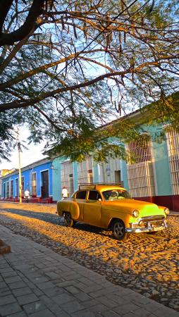 empedrado: Coche amarillo en calle pavimentada Trinidad, Cuba