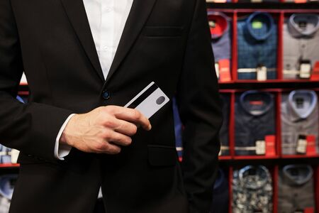 man in jacket holding a credit card